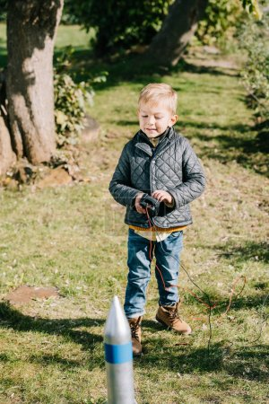 adorable child launching model rocket outdoor