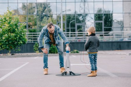 father and little son playing with model rocket together