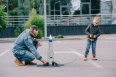 father and little son playing with model rocket outdoor