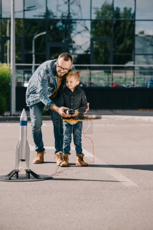 happy father and son launching model rocket outdoor