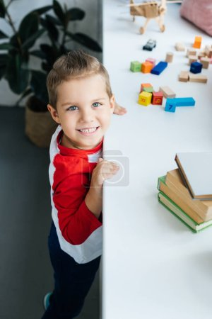 Photo for High angle view of child standing at surface with books and colorful blocks at home - Royalty Free Image