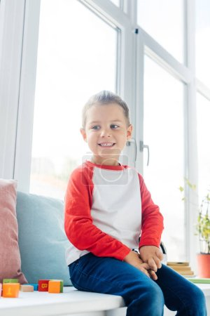 Photo for Portrait of cute cheerful boy sitting at window at home - Royalty Free Image