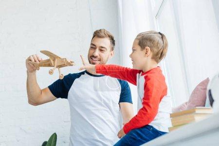 Foto de Muchacho quiere coger avión de juguete de madera de mano de fatehrs en casa - Imagen libre de derechos