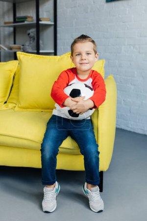 Foto de Niño con balón en las manos apoyadas sobre el sofá amarillo en casa sonriente - Imagen libre de derechos