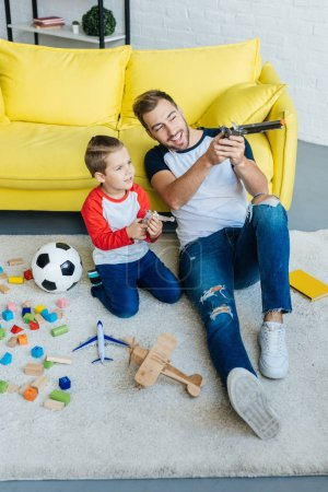 smiling man and cute son playing with toys together on floor at home