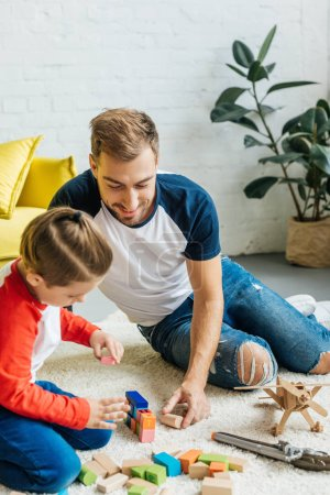 father and cute little son playing with wooden blocks together at home