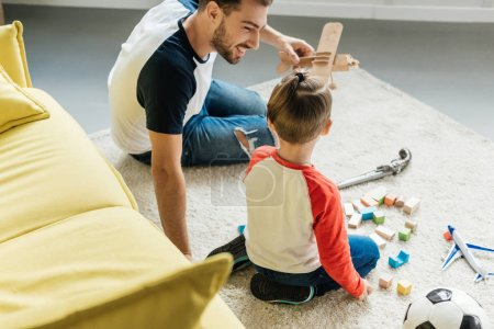 father and cute little son playing with wooden blocks together on floor at home