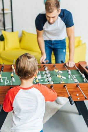 Photo pour Père et fils jouer baby-foot ensemble à la maison - image libre de droit