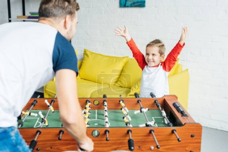 happy little boy playing table football together with father at home