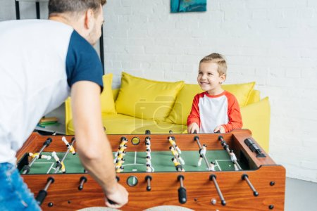 Photo for Partial view of father and son playing table football together at home - Royalty Free Image