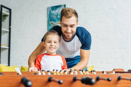 Photo for Smiling father and son playing table football together at home - Royalty Free Image
