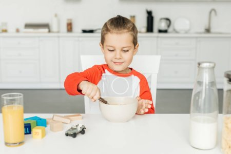 portrait of little boy having breakfast in kitchen at home