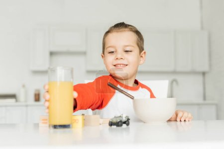Photo for Smiling boy having breakfast in kitchen at home - Royalty Free Image