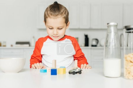 little boy playing with toys in kitchen at home
