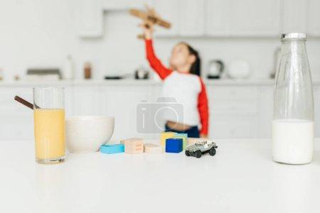 Foto de Enfoque selectivo de niño jugando con plano de madera del juguete en cocina en casa - Imagen libre de derechos