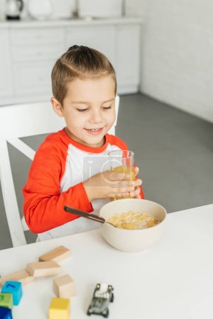 portrait of child with glass of juice having breakfast in kitchen at home