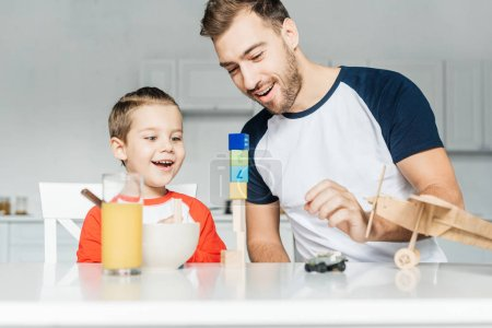 handsome young father and son playing with toys on kitchen at home