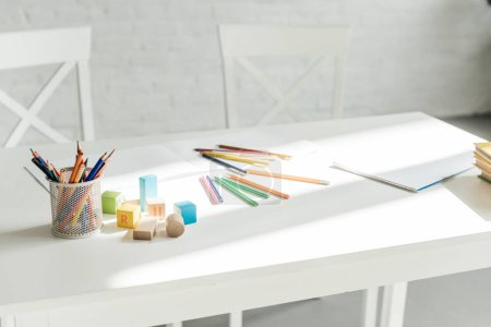close-up shot of color pencils with blank album and wooden blocks lying on table