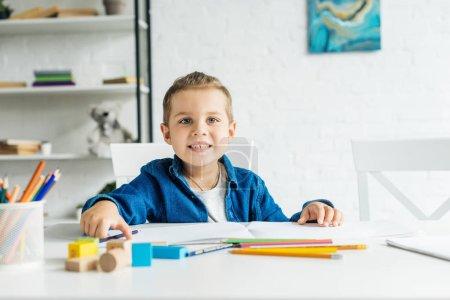 Photo pour Sourire de petit enfant dessin aux crayons de couleur à la maison et regarder la caméra - image libre de droit