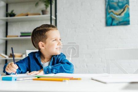 Photo pour Mignon petit enfant dessin aux crayons de couleur à la maison et de la recherche. - image libre de droit