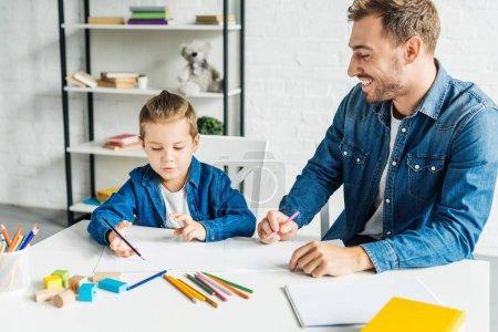 Photo pour Heureux jeune père dessin avec adorable petit fils à la maison - image libre de droit