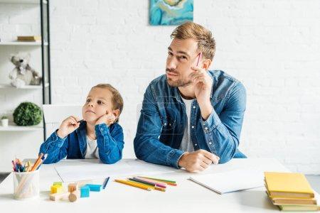 Photo pour Gentil jeune père dessiner avec petit fils à la maison - image libre de droit