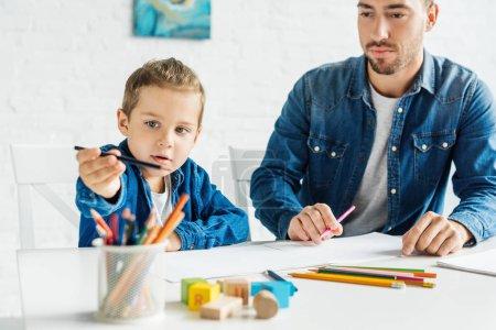 Photo pour Beau jeune père dessin avec adorable petit fils à la maison - image libre de droit