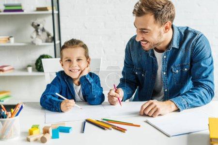 Photo pour Beau jeune père dessin avec fils peu souriant à la maison - image libre de droit