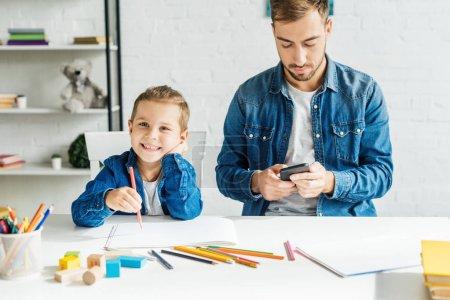 Photo pour Beau jeune père à l'aide de smartphone tout en dessinant à la maison de fils - image libre de droit