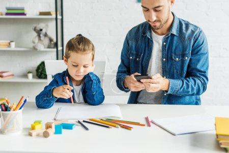 Photo pour Jeune père à l'aide de smartphone tout en dessinant à la maison de fils - image libre de droit