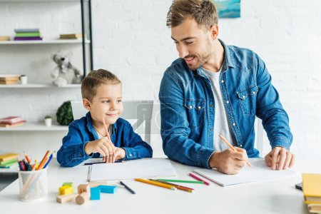 happy young father drawing with son at home