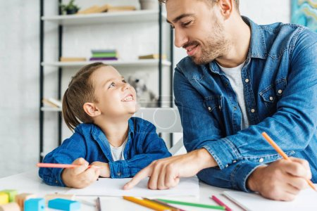 Photo for Smiling young father drawing with son at home - Royalty Free Image
