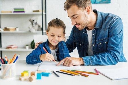 Photo pour Beau jeune père dessin avec des fils à la maison - image libre de droit