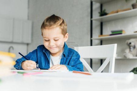 smiling little child drawing with color pencils at home