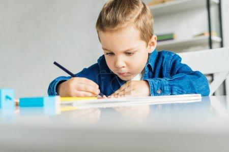 concentré de petit enfant dessin aux crayons de couleur à la maison