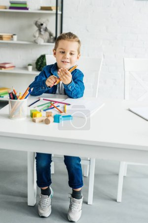 Photo pour Heureux petit enfant dessin aux crayons de couleur à la maison - image libre de droit