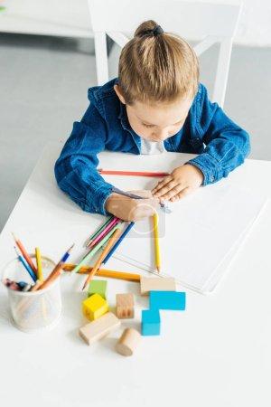 vue de la forte inclinaison du petit enfant dessin aux crayons de couleur à la maison