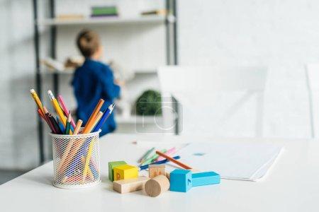 Photo pour Crayons de couleur et des blocs de bois sur table avec l'ordinateur portable posé sur table avec petit enfant floue sur fond - image libre de droit