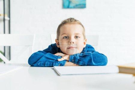 Photo pour Adorable petit enfant assis à table avec cahier vierge et regardant la caméra - image libre de droit