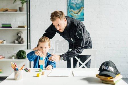 Photo pour Jeune père en uniforme de policier et son fils jouer ensemble à la maison - image libre de droit