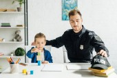 handsome young father in police uniform and son playing together at home