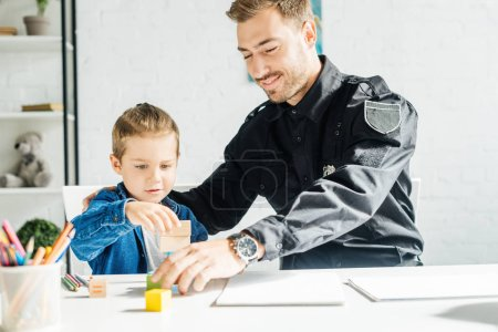 Foto de Feliz joven padre en uniforme de policía e hijo jugando juntos en el hogar - Imagen libre de derechos