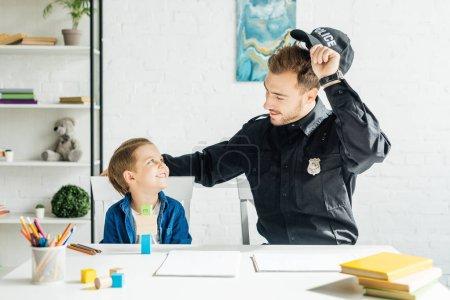 Foto de Sonriente joven padre en uniforme de policía y su hijo pasar tiempo juntos en casa - Imagen libre de derechos