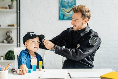 Foto de Feliz joven padre en uniforme de policía y su hijo pasar tiempo juntos en casa - Imagen libre de derechos