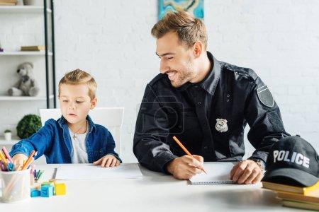 Foto de Feliz joven padre en uniforme de policía y su hijo pequeño dibujo juntos en casa - Imagen libre de derechos