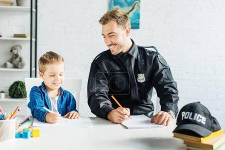 Photo pour Souriantes jeune père en uniforme de policier et fils réunissant à la maison - image libre de droit