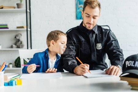 Photo pour Beau jeune père en uniforme de policier et fils réunissant à la maison - image libre de droit