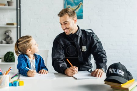 Photo pour Heureux jeune père en uniforme de policier et fils réunissant à la maison - image libre de droit