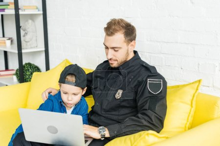 handsome young father in police uniform and son using laptop together while sitting on yellow couch at home