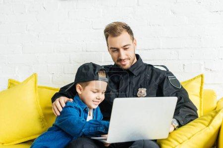 Photo pour Beau jeune père en uniforme de police et fils utilisant ordinateur portable ensemble tout en étant assis sur le canapé jaune à la maison - image libre de droit